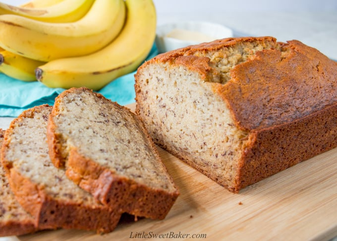 A loaf of bananan bread with a few slices cut on a wooden cutting board.