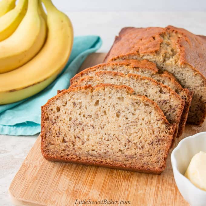 A loaf of banana bread with a three slices cut on a cutting board.
