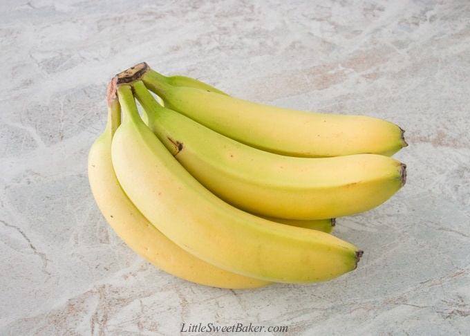 A yellow-green bunch of bananas on marble.