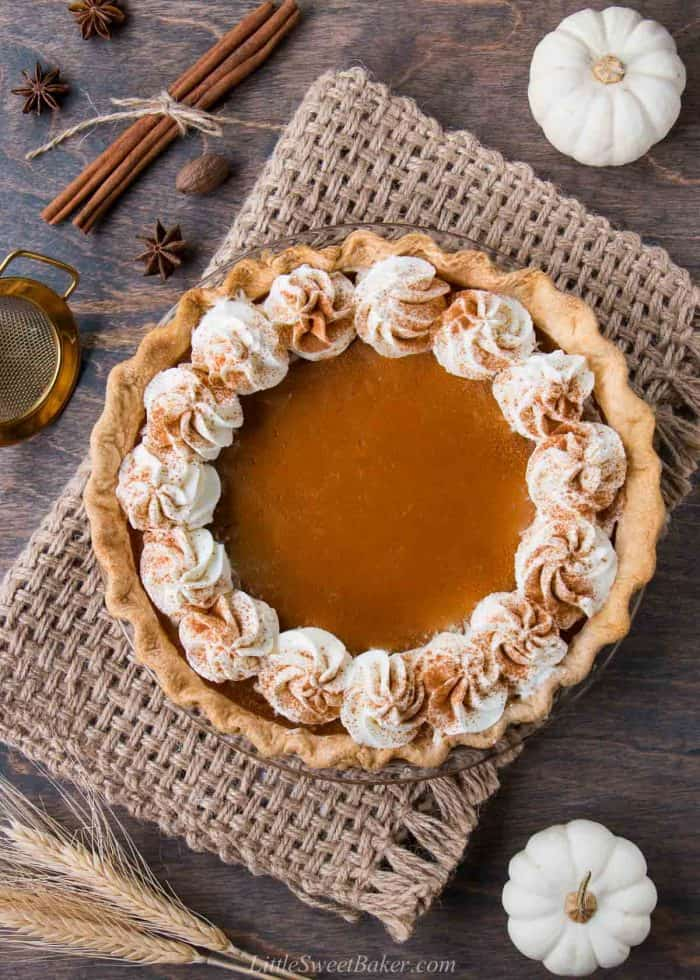 A pumpkin pie topped with whipped cream along the edge on a piece of burlap.