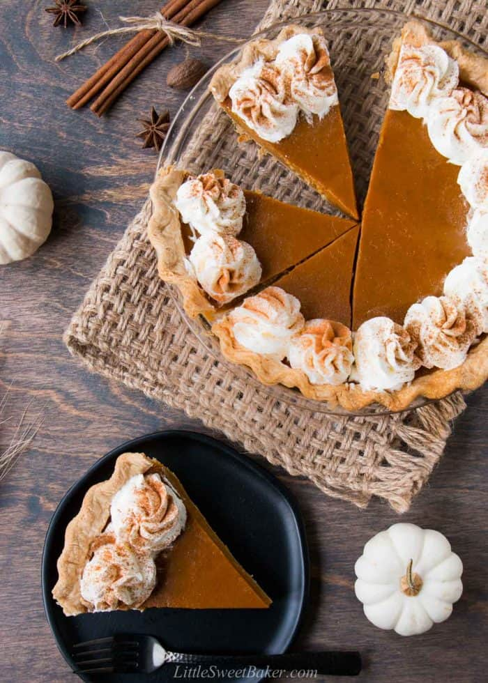 Pumpkin pie with half cut and a slice on a plate.