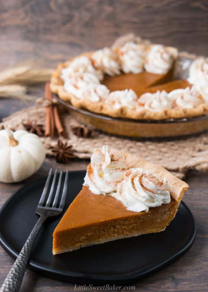 A slice of pumpkin pie with whipped cream on a black plate.