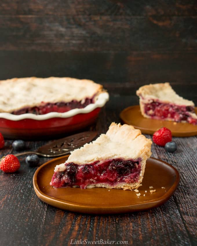 A slice of mixed berry pie on a wooden plate.