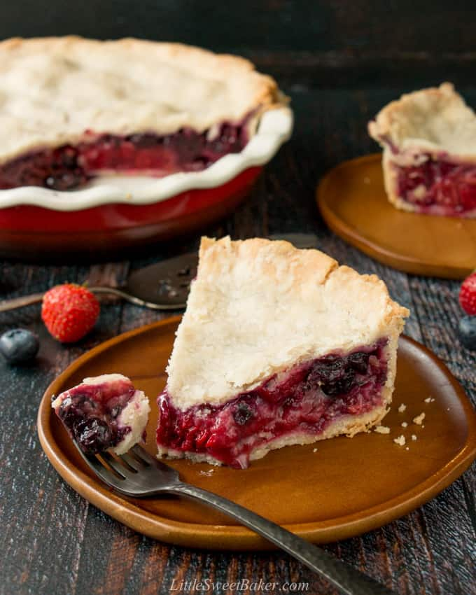 A slice of mixed berry pie on a wooden plate with a piece on a fork.