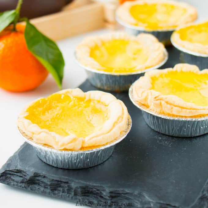 Chinese egg tarts on a black slate board with a mandarin orange in the background.