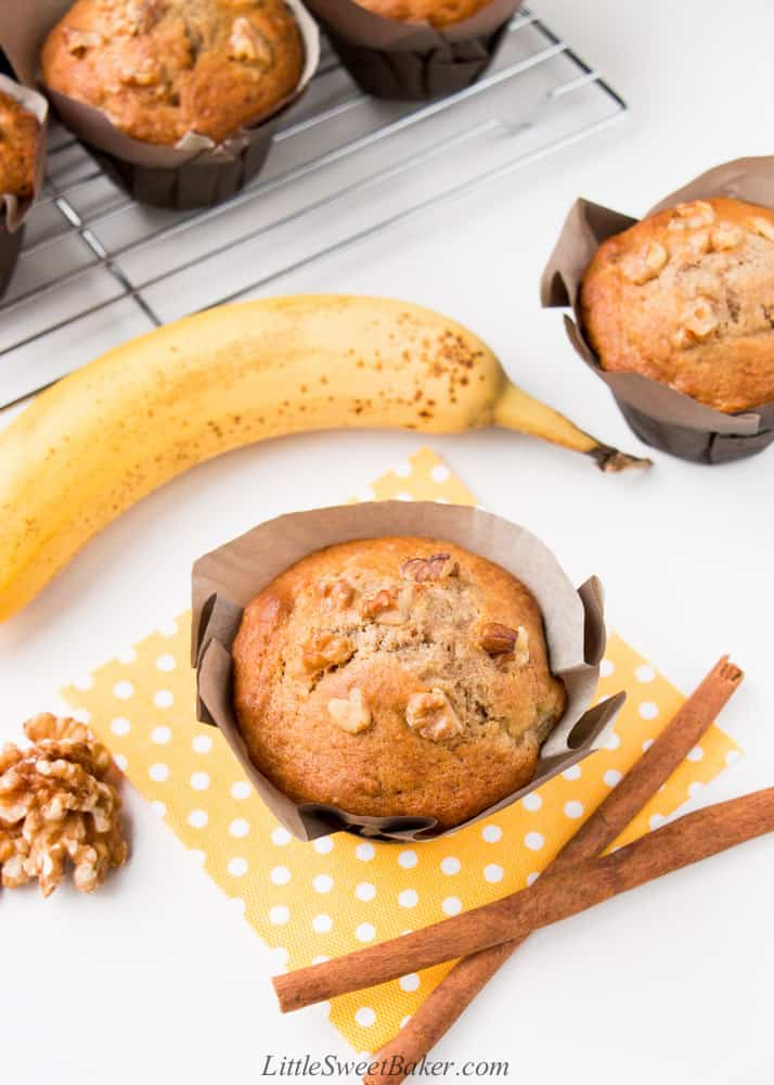 A banana nut muffin on a yellow napkin with two cinnamon sticks, banana, and walnuts.