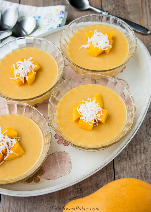 Four bowls of mango pudding topped with diced mangoes and coconut on a plate.