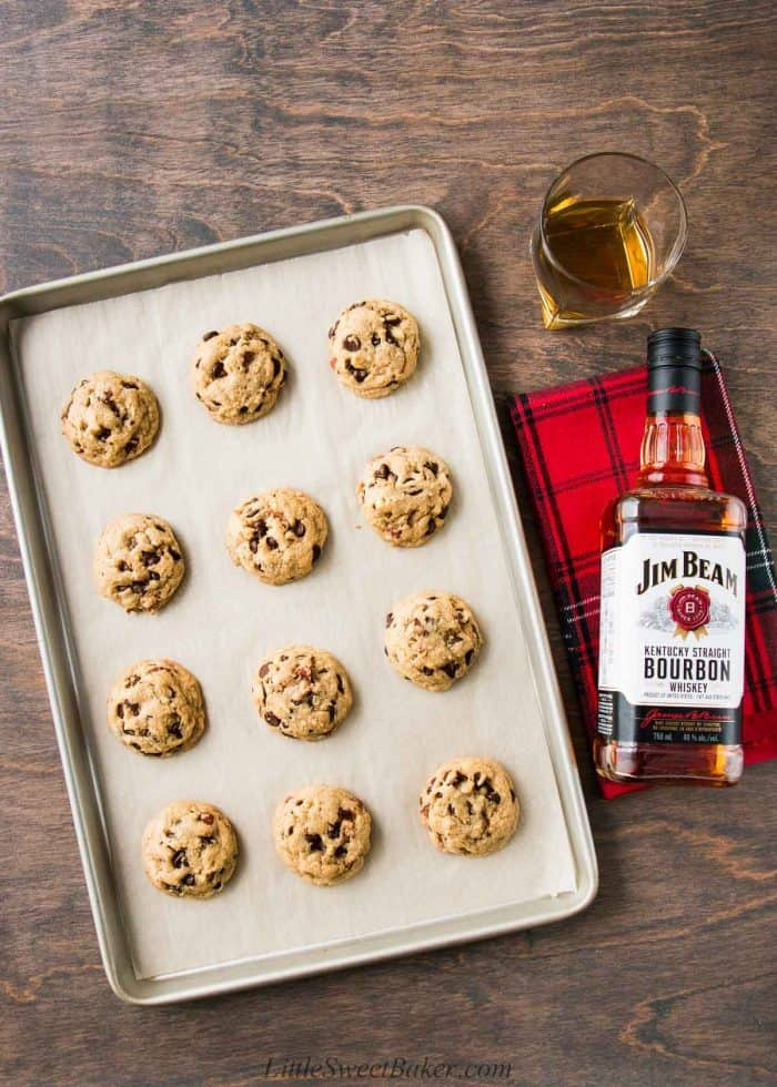 A tray of bourbon chocolate chip cookies with a bottle of bourbon on a wooden table.