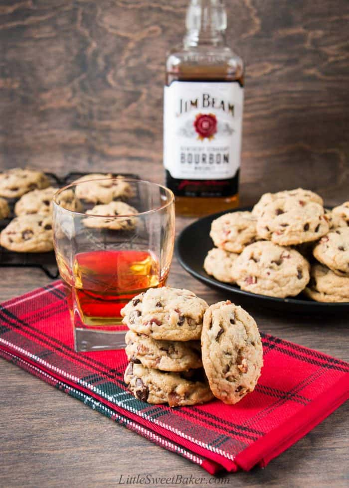 Bourbon bacon chocolate chip cookies on a red napkin with a glass of bourbon.