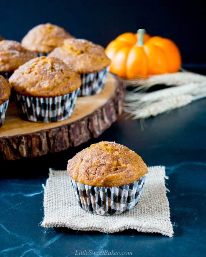 A pumpkin spice muffin on a piece of burlap with a wooden tray of muffins behind.