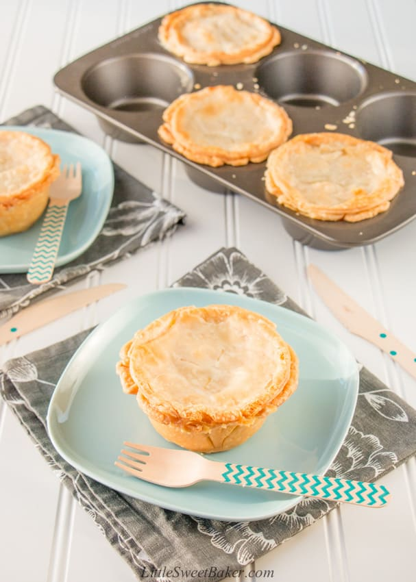 Two mini turkey pot pies on a plate and three mini turkey pot pies in a jumbo muffin pan.