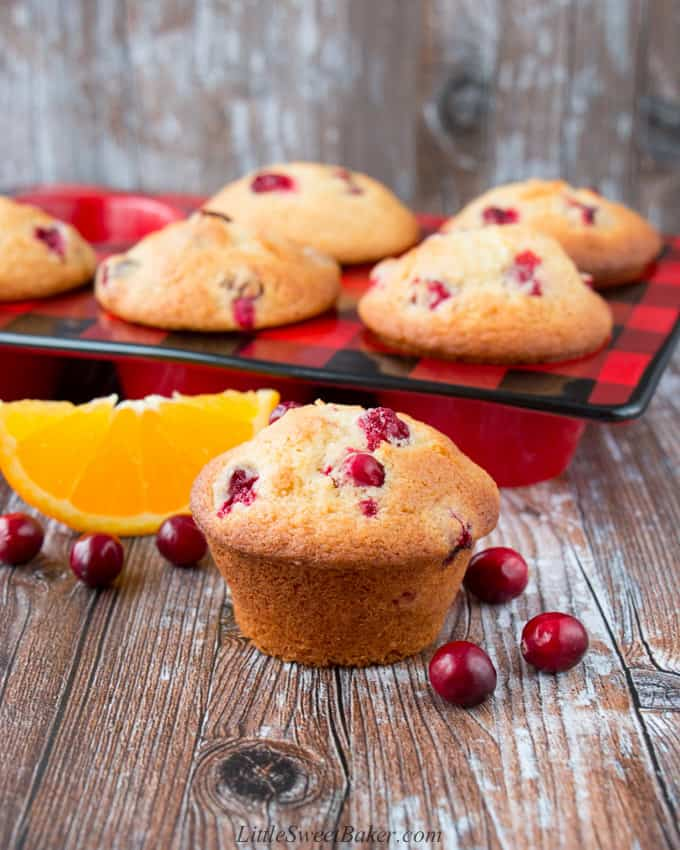 A cranberry orange muffin surrounded by cranberries and an orange wedge on a wooden surface.