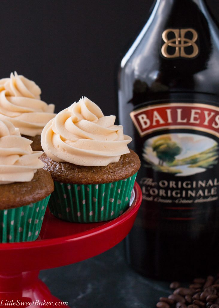 Baileys and coffee cupcakes on a red stand with a bottle of Baileys