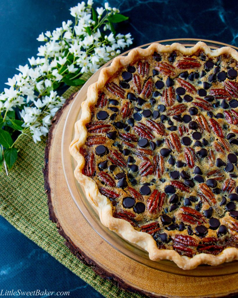 a chocolate pecan pie on a wooden board and green dish towel
