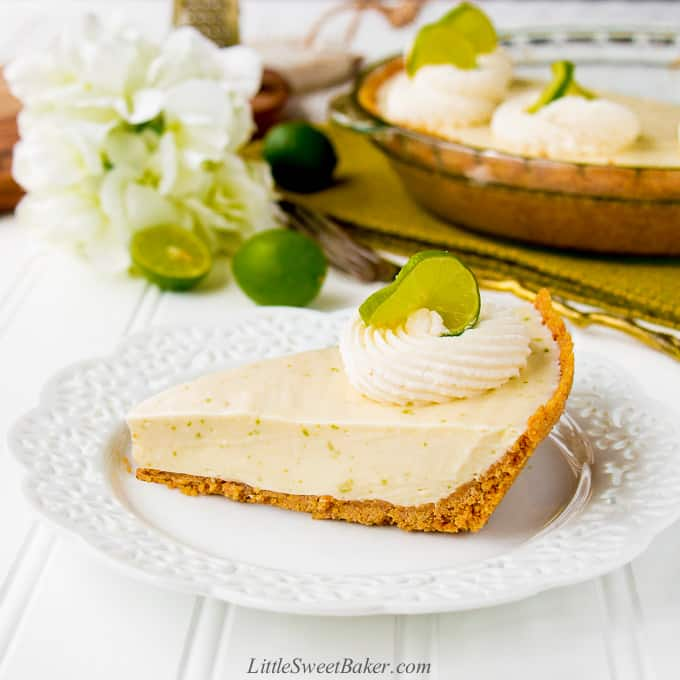 A slice of key lime pie on a white plate with the rest of the pie, white flower and key limes in the background.