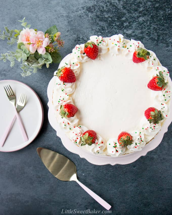 A top view of a no-bake cheesecake topped with whipped cream, strawberries and sprinkles.