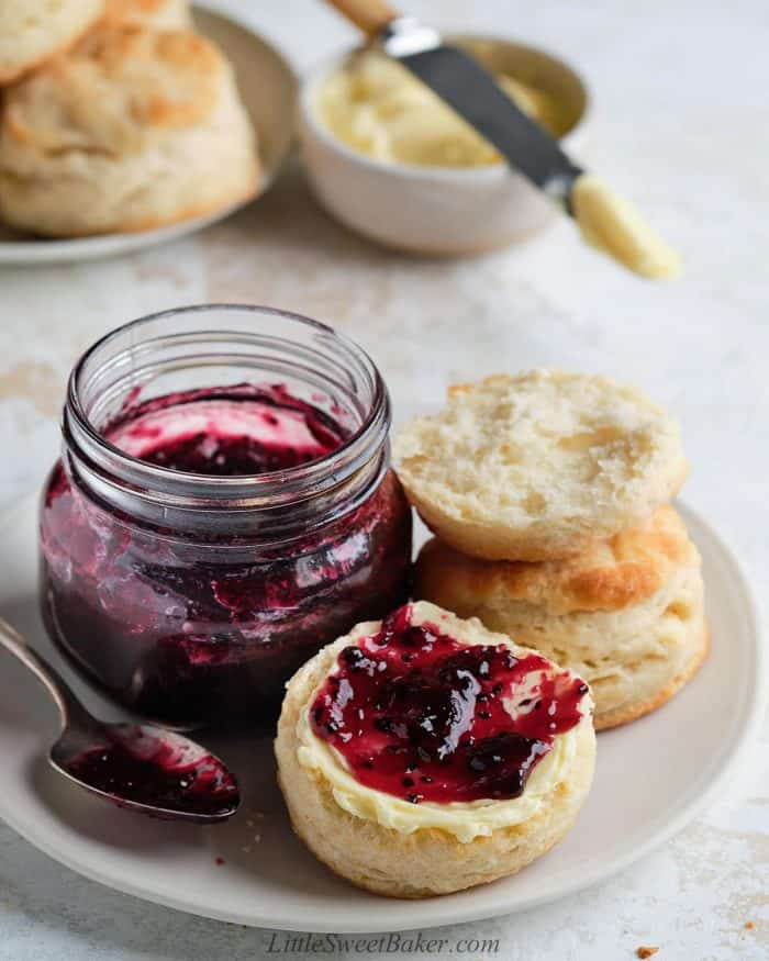 Two biscuits on a plate with a jar of jam. One biscuit with clotted cream and jam on it.