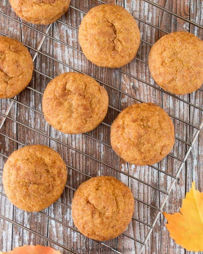 Pumpkin spice cookies on a cooling rack on a wooden background.