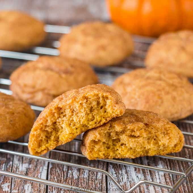 Pumpkin spice cookies on a cooling rack with one broken in half.