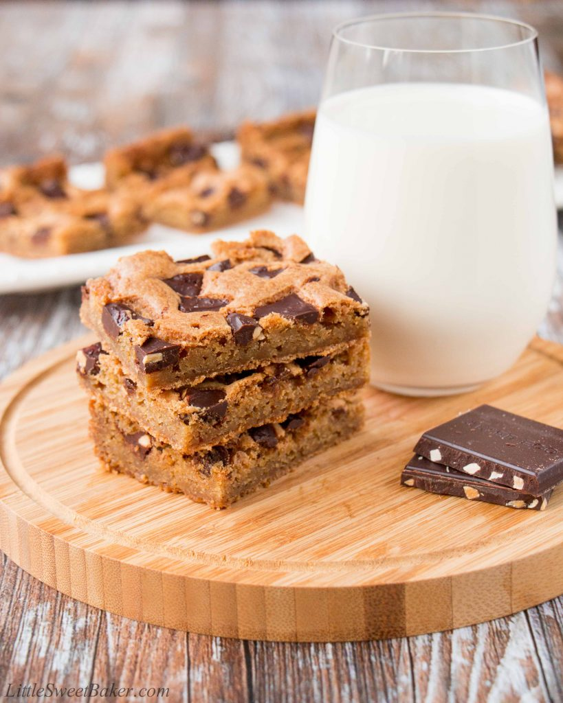 These chewy chocolate chunk cookie bars are so much easier to make than cookies. One bowl, one pan and done! #chocolatechipcookiebars #cookiebars #christmascookies #chocolatechunkcookies #chocolatechunkcookiebars