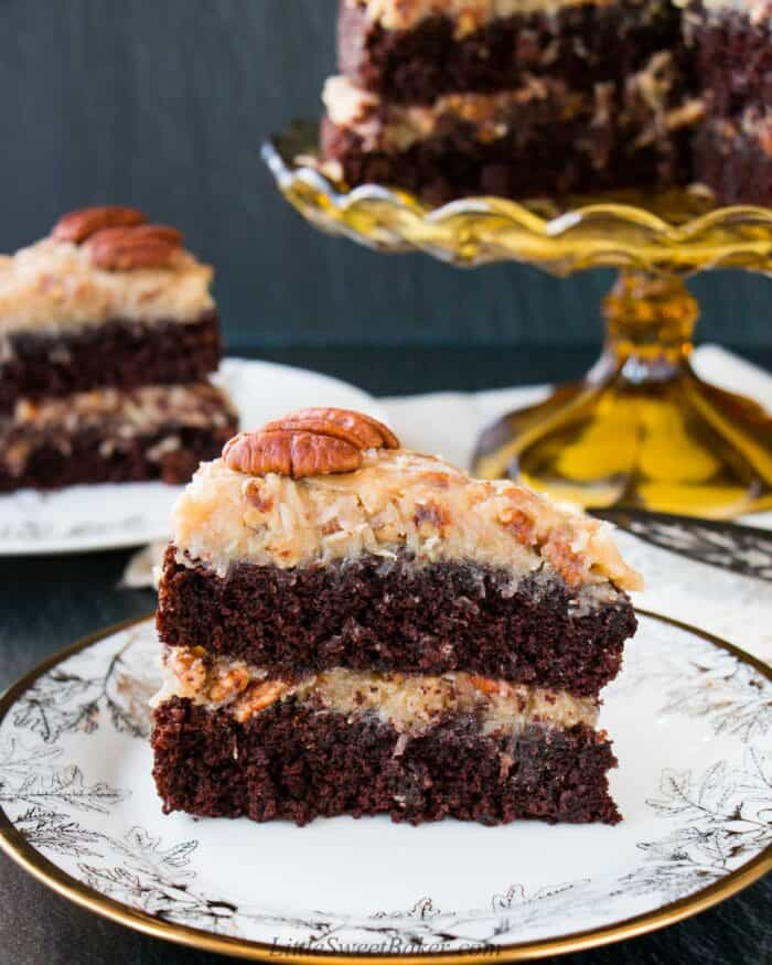 A slice of German chocolate cake on a white and gold plate.