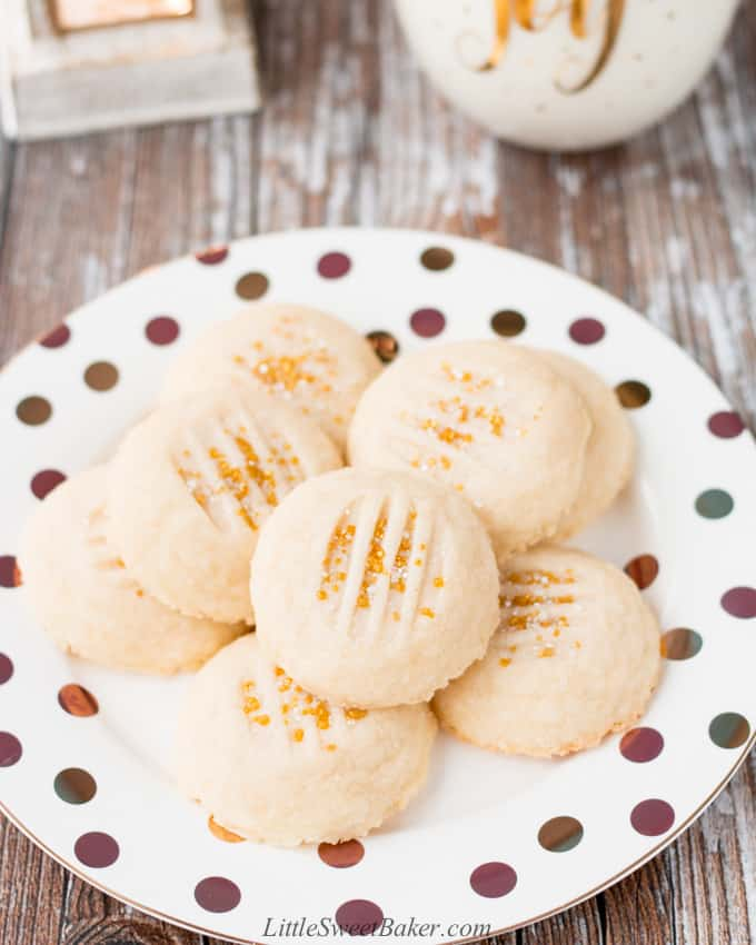 A plate of whipped shortbread cookies with gold sprinkles.