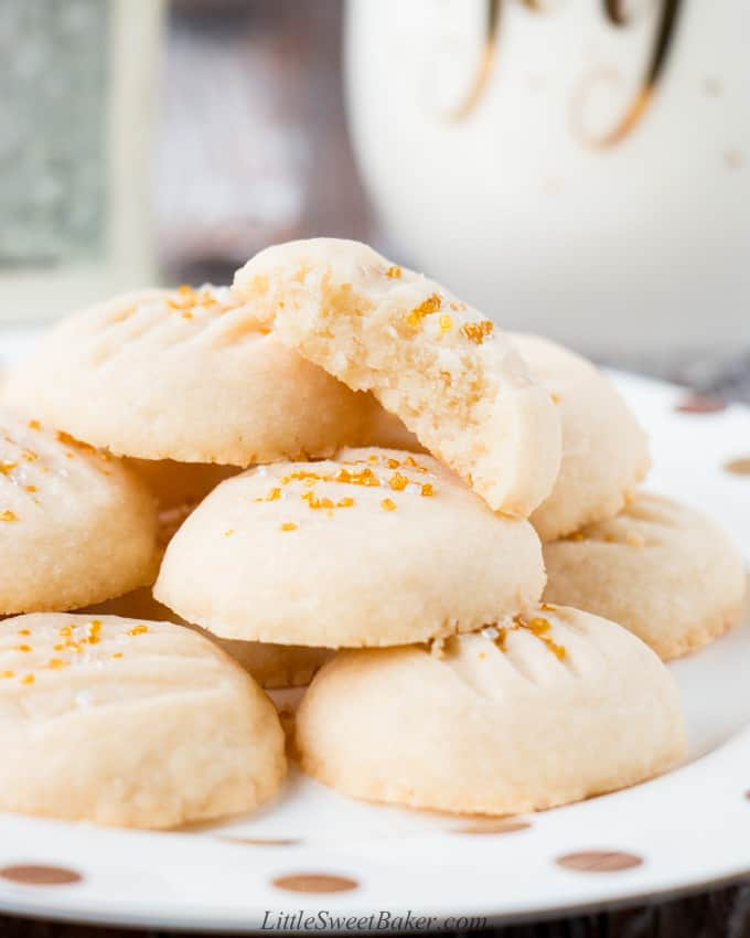A plate of whipped shortbread cookies with one broken in half.