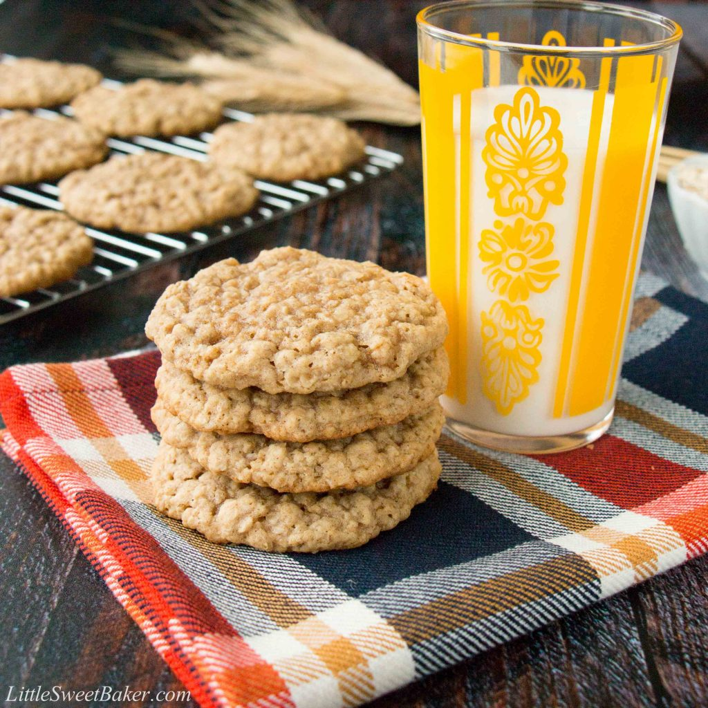 A stack of oatmeal cookies on a plaid napkin with a glass of milk.