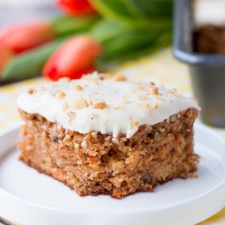 This delicious carrot cake is easy to make, moist and tender. It's speckled with shredded carrots, pineapple chunks, walnuts and topped with a sweet-tangy cream cheese frosting. #carrotcake #carrotcakerecipe #easycarrotcake