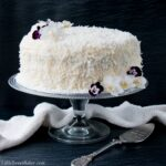 This delicious made-from-scratch coconut cake is infused with natural coconut flavor and topped with a sweet-tangy cream cheese frosting. #coconutcake #southerncoconutcake #bestcoconutcake #inagartencoconutcake #easycoconutcake #easterdessert