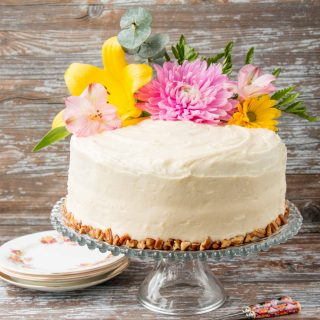 Coated in a delicious cream cheese frosting, this supremely moist banana cake has sweet pieces of pineapples and crunchy pecans mixed in. It's spiced with cinnamon and nutmeg, and sweetened with brown sugar. #hummingbirdcake #layercake #creamcheesefrosting #bananacake