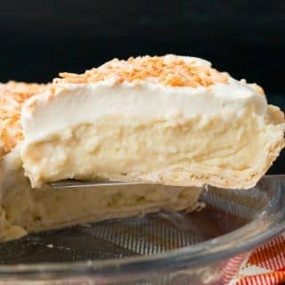 This homemade coconut cream pie is made with coconut milk and shredded coconut for the most flavorful and delicious custard filling you've ever tasted!#coconutcreampie #coconutmilk #flakypiecrust #Thanksgivingdessert