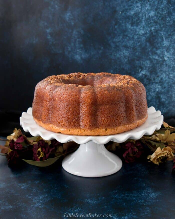 A whole Bacardi rum cake on a white cake stand with flowers and a dark blue background.