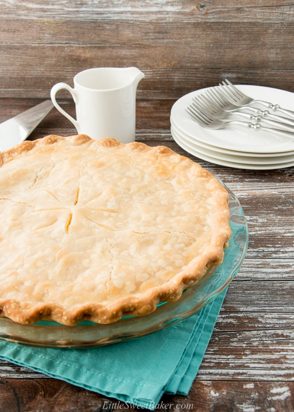 whole chicken pot pie in a glass plate on a teal napkin