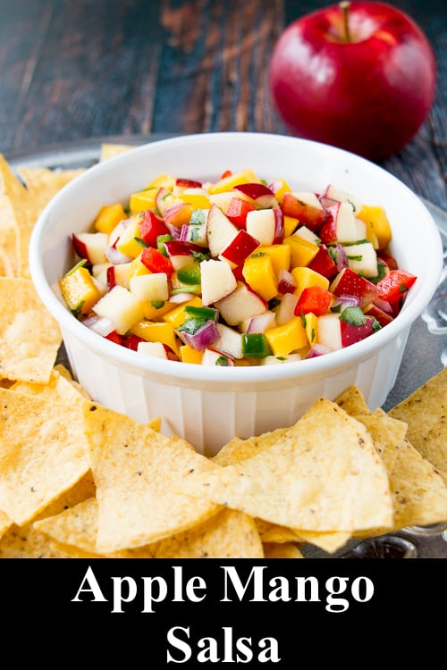 apple mango salsa in a white bowl surrounded by tortilla chips