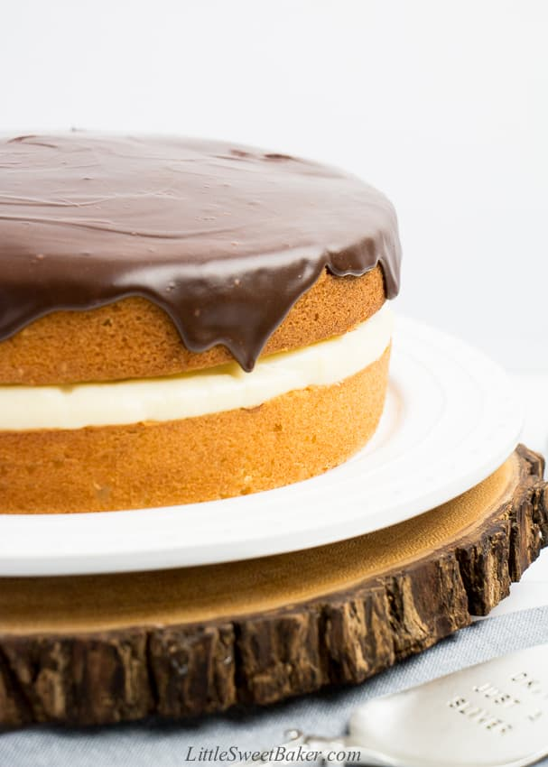 A close-up of a Boston cream pie on a white plate and wooden board.