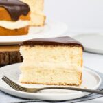 A slice of Boston cream pie on a light grey plate with fork.