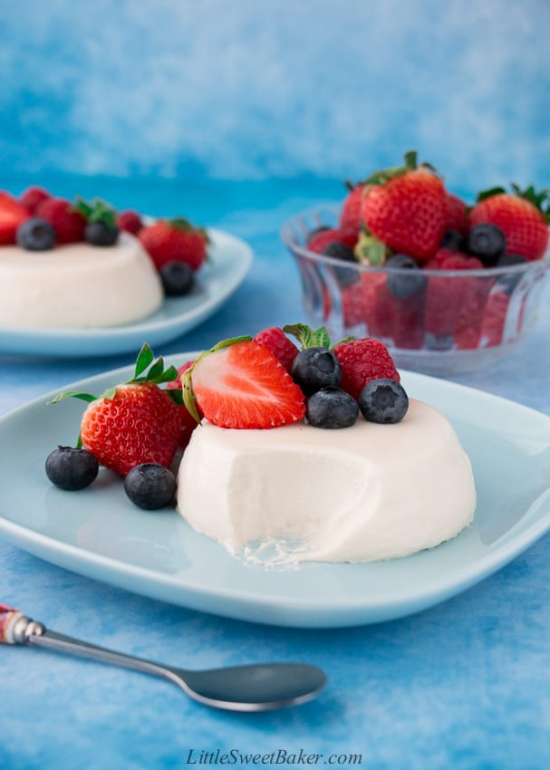 partially eaten panna cotta with berries on a blue plate
