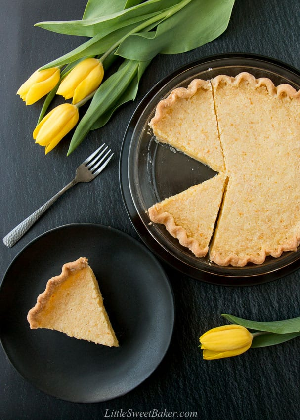 A lemon pie and slice on a black plate with yellow tulips and a dark grey fork.