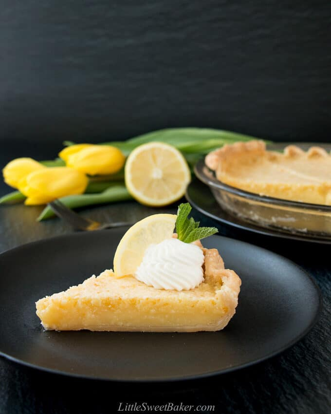 A slice of lemon pie on a black plate with whipped cream, lemon wedge and yellow tulips in the background.