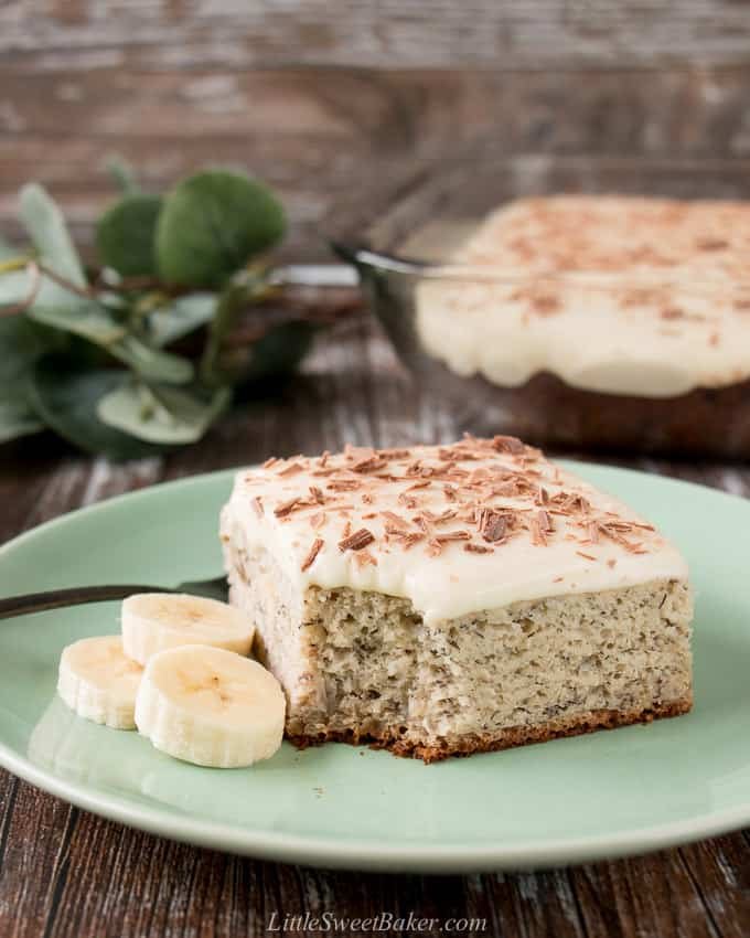 A slice of banana cake topped with cream cheese frosting on a green plate with some fresh banana slices.