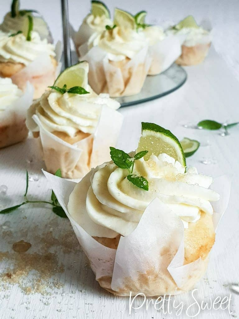 mojito cupcakes with white liners topped with lime and mint