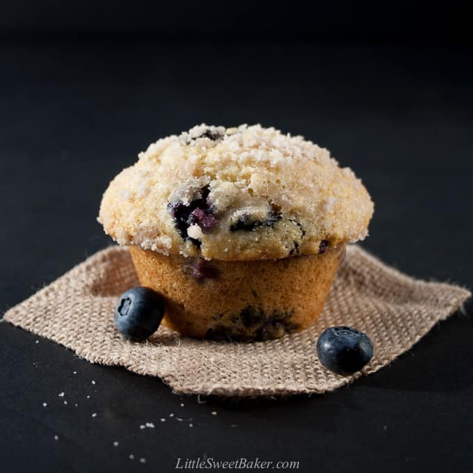A blueberry streusel muffin on a piece of burlap with two blueberries.