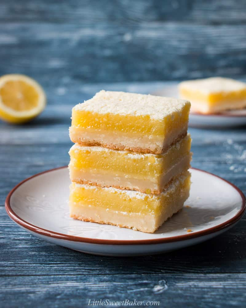A triple stack of lemon bars on a light gray plate with a blue background.