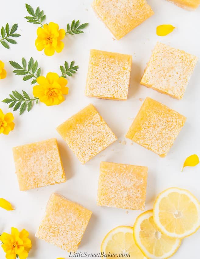 Overhead view of lemon bars on a white board with yellow flowers and lemon slices.