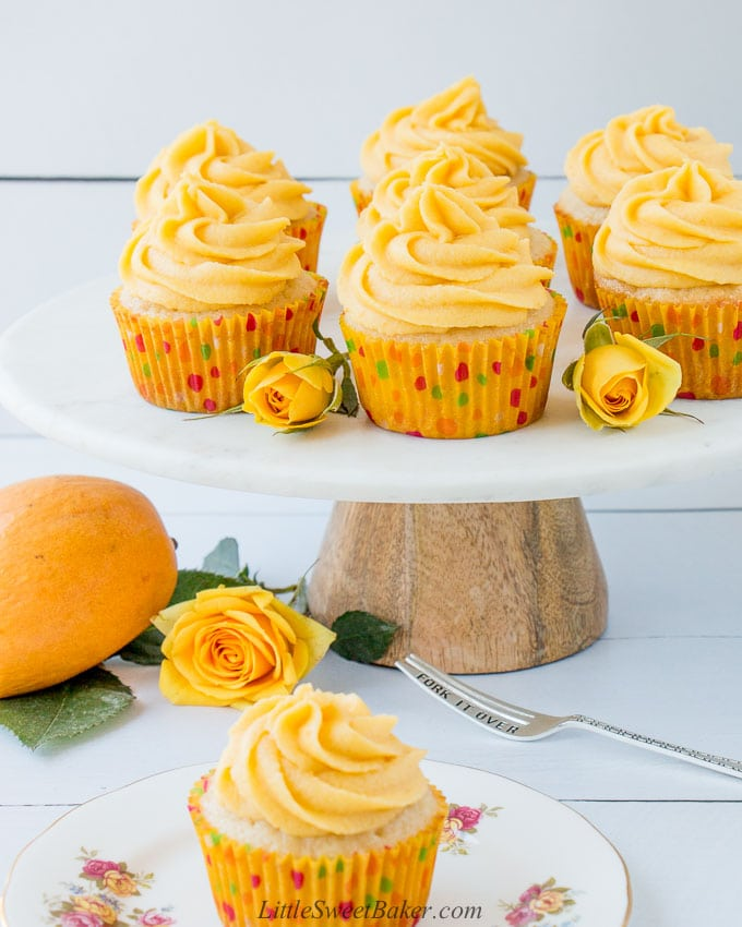 Mango cupcakes on a marble cake stand with yellow roses.