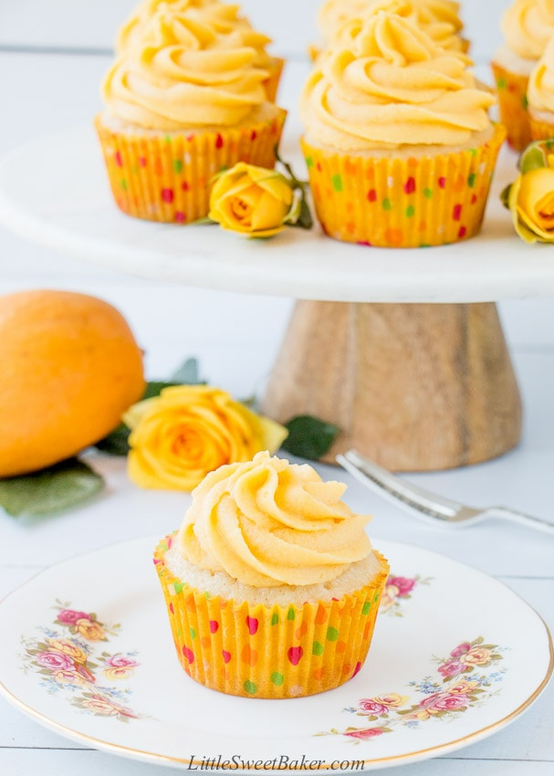 A mango cupcake on a white floral plate with a stand of cupcakes in the background.