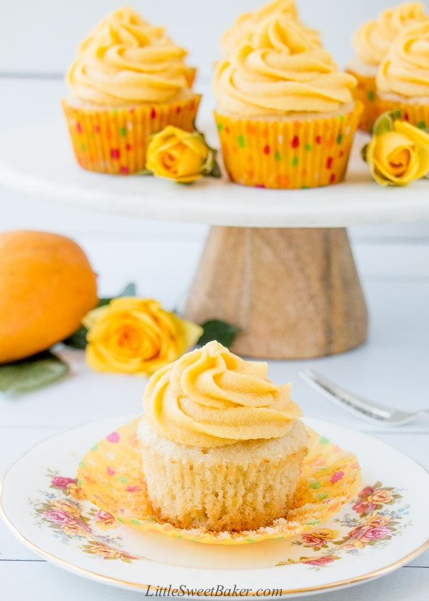 A mango cupcake on a white plate with the paper liner peeled back.