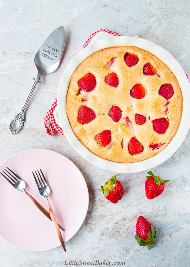 A whole strawberry cake with a pink plate, forks, cake serve and strawberries.