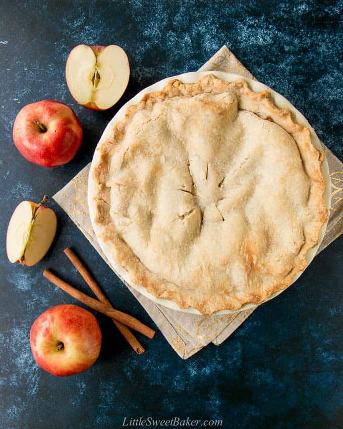 A whole apple pie on a beige napkin surrounded by apples and cinnamon sticks.